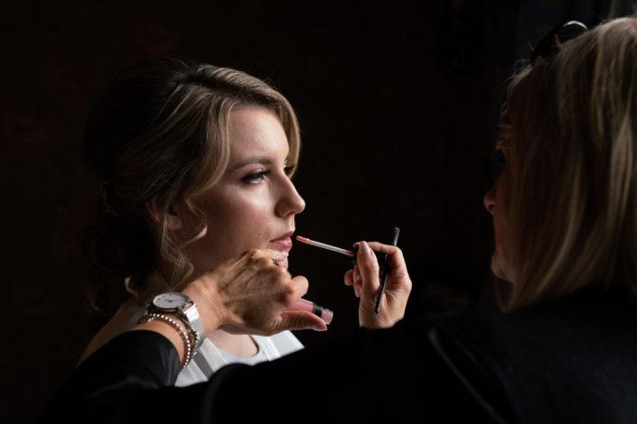makeup artist applying lipstick to a bride