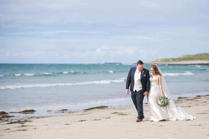 couple walking on the beach for wedding photos