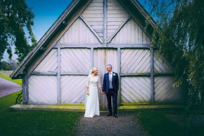 couple pose for wedding photos at a boathouse