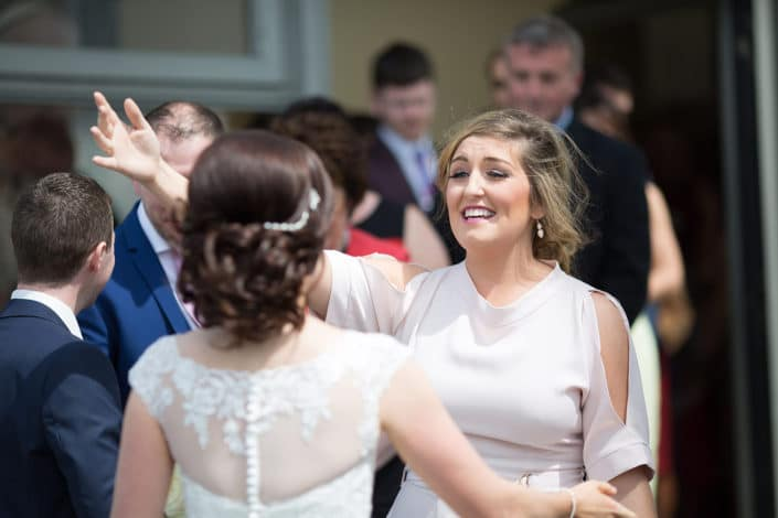 wedding guest congratulates bride outside church in mayo