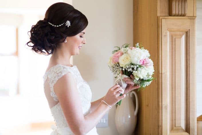 bride looking at flower bouquet