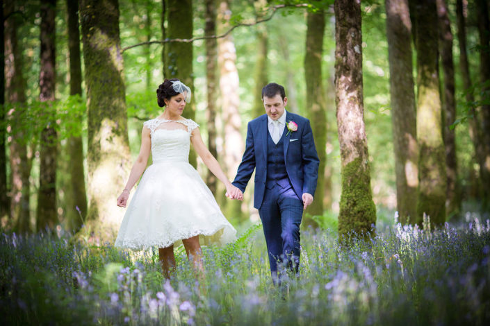 bride and groom walking through bluebell woods near kilronan castle