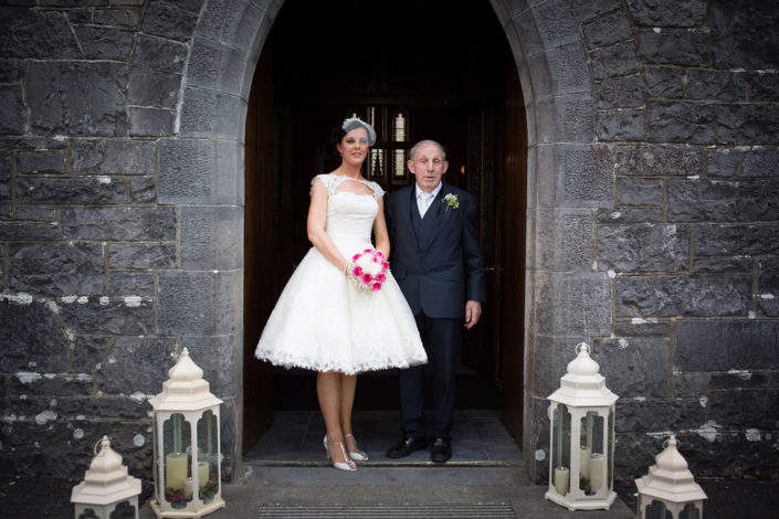 father of the bride and bride in knee length dress at church door
